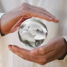 Crystal globe floating between a mans hands